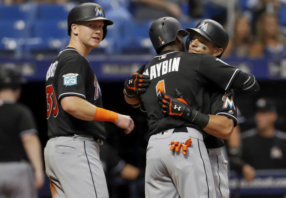 Miami Marlins' Derek Dietrich, right, is congratulated by Cameron Maybin (1) and Garrett Cooper after his three-run home run scored them all during the seventh inning of a baseball game against the Tampa Bay Rays on Friday, July 20, 2018, in St. Petersburg, Fla. (AP Photo/Mike Carlson)