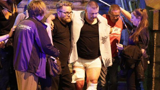 PHOTO: People aid an injured man near the Manchester Arena after reports of an explosion, May 22, 2017. (Joel Goodman/LNP/REX/Shutterstock)