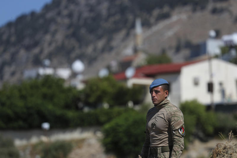 A Turkish commando stands guard in the area after an explosion pre-dawn, outside of the village of Tashkent in Turkish Cypriot breakaway north part of the divided Cyprus, Monday, July 1, 2019. A Turkish Cypriot official said Monday that a Syrian anti-aircraft missile that missed its target and reached ethnically divided Cyprus may have been the cause of an explosion outside a village in east Mediterranean island notion's breakaway north. No injuries were reported. (AP Photo/Petros Karadjias)