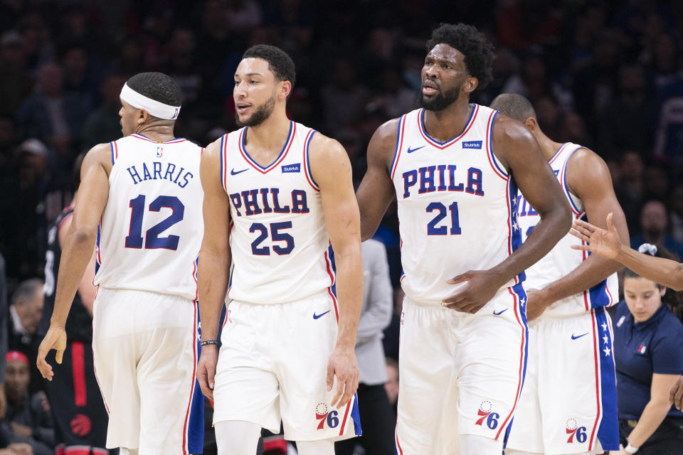 Tobias Harris #12, Ben Simmons #25, and Joel Embiid #21 of the Philadelphia 76ers react against the Toronto Raptors at Wells Fargo Center on December 8, 2019 in Philadelphia, Pennsylvania.