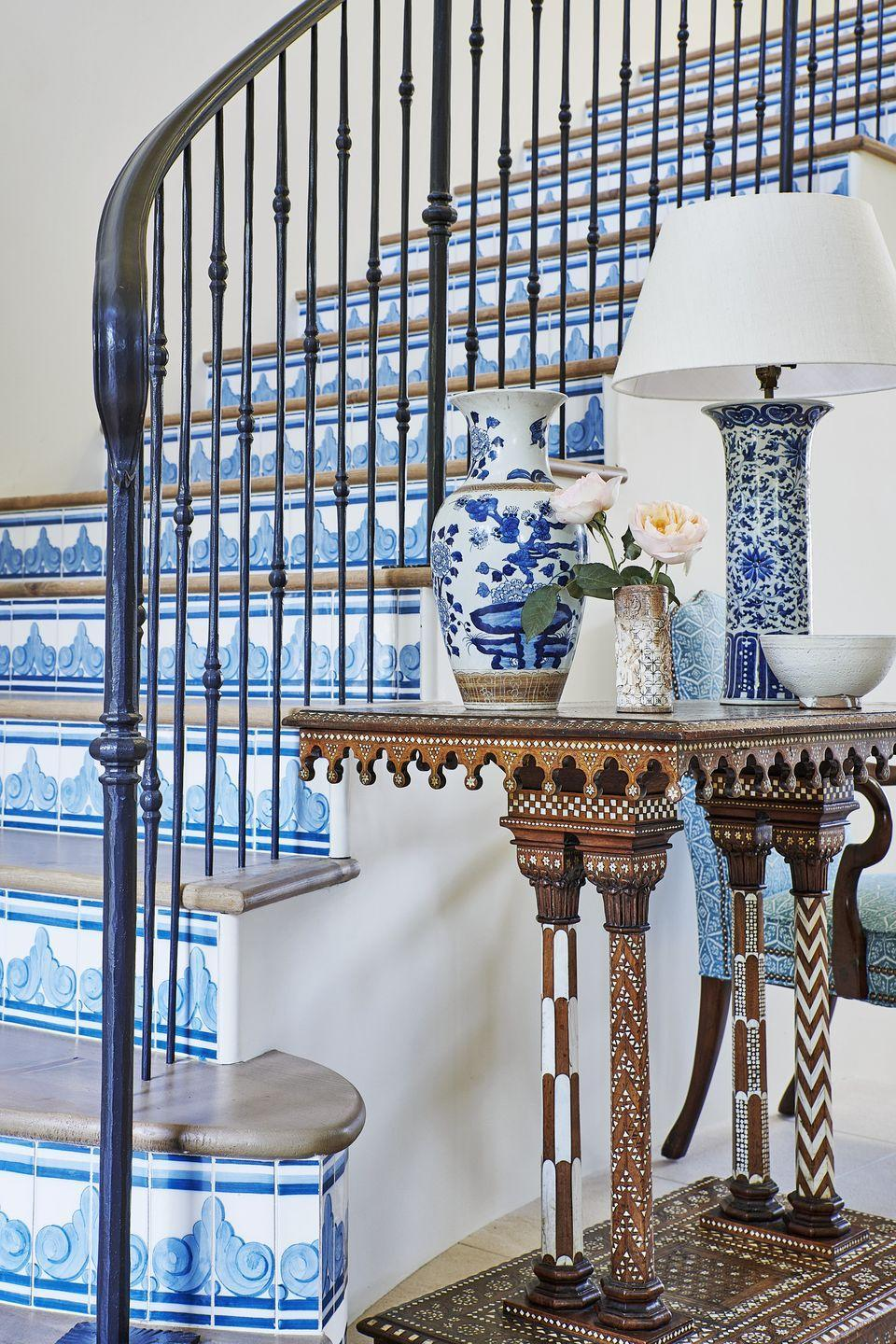 """<p>It's no secret designer Mark D. Sikes loves to pair blue and white in his projects, and that's just the case in <a href=""""https://www.veranda.com/decorating-ideas/house-tours/a34244492/mark-sikes-california-house-tour-2020/"""" rel=""""nofollow noopener"""" target=""""_blank"""" data-ylk=""""slk:fashion designer Karen Kane's home in Pacific Palisades"""" class=""""link rapid-noclick-resp"""">fashion designer Karen Kane's home in Pacific Palisades</a>. Here, Sikes utilizes hand-painted ceramic tiles from NC Ceramic, offering a beautiful alternative to actually painting the stairs themselves while still creating visual interest and introducing more pattern.</p>"""