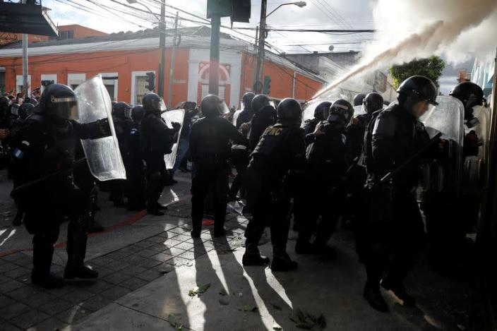 Riot police spray a fire extinguisher at demonstrators during a protest demanding the resignation of President Alejandro Giammattei, in Guatemala City