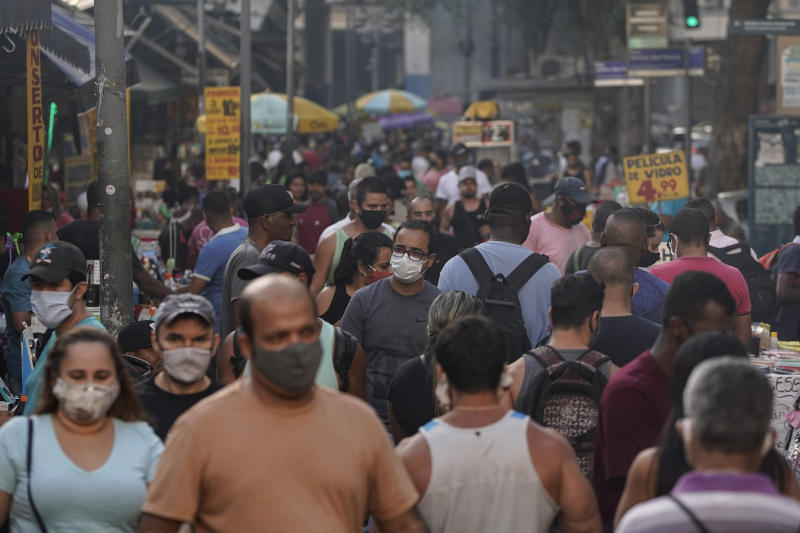 Pedestrians, some wearing protective face masks, walk through a street market in downtown in Rio de Janeiro, Brazil, Thursday, June 25, 2020. Rio continues with its plan to ease restrictive measures due to the new coronavirus and open up the economy to avoid an even worse economic crisis. (AP Photo/Leo Correa)