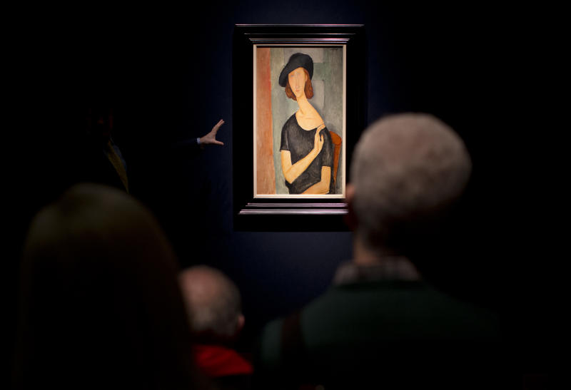 "The gesturing hand of an expert speaking to a group of people is lit by a spotlight illuminating the painting entitled ""Jeanne Hebuterne (Au chapeau)"" by Italian artist Amedeo Modigliani at Christie's auction house in London, Friday, Feb. 1, 2013. The piece is estimated to fetch between 16 and 22 million pounds ($25.3 to $34.8 million or 18.5 to 25.5 million euro) in the forthcoming Impressionist and Modern Art evening sale in London on February 6.  (AP Photo/Matt Dunham)"