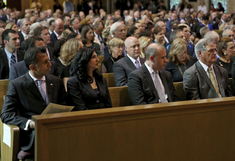 From the left, former Louisiana Governor Bobby Jindal and his wife Supriya, former New Orleans Mayor Mitch Landrieu, and New Orleans Saints general manager Mickey Loomis  listen during a Celebration of Life Interfaith Service for former Louisiana Gov. Kathleen Babineaux Blanco, at St. Joseph Cathedral in Baton Rouge, La., Thursday, Aug. 22, 2019. Thursday was the first of three days of public events to honor Blanco, the state's first female governor who died after a years long struggle with cancer.(AP Photo/Michael Democker, Pool)