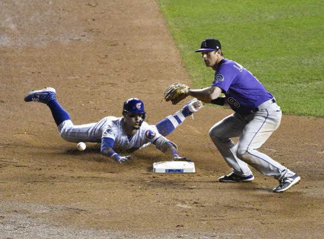 Chicago Cubs' Javier Baez, left, slides into second base safely as he hit a one-run double as Colorado Rockies second baseman DJ LeMahieu (9) makes a late tag during the eighth inning of the National League wild-card playoff baseball game, Tuesday, Oct. 2, 2018, in Chicago. (AP Photo/David Banks)