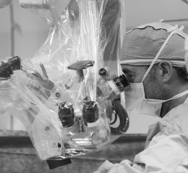 Dr. Sean Barry is shown operating using a surgical microscope.