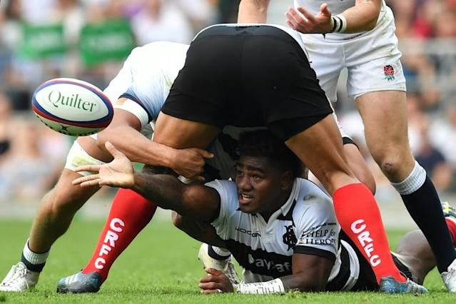 Barbarians wing Josua Tuisova (C) passes the ball from the floor during the international friendly rugby union match between England and the Barbarians at the Twickenham, west London (AFP Photo/Ben STANSALL)