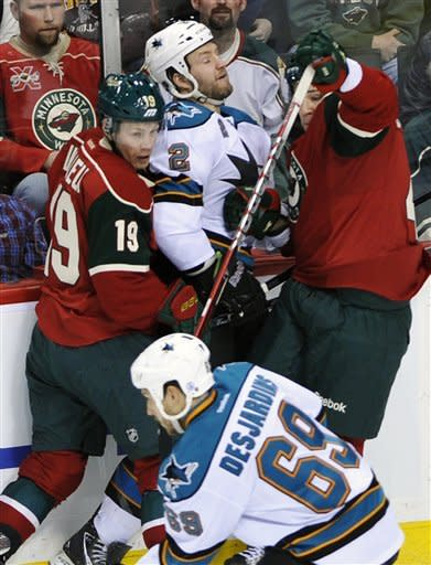 Minnesota Wild's Stephane Veilleux, left, and another teammate tie up San Jose Sharks' Jim Vandermeer (2) as Sharks' Andrew Desjardins, bottom, races with the puck in the first period of an NHL hockey game, Sunday, Feb. 26, 2012, in St. Paul, Minn. (AP Photo/Jim Mone)