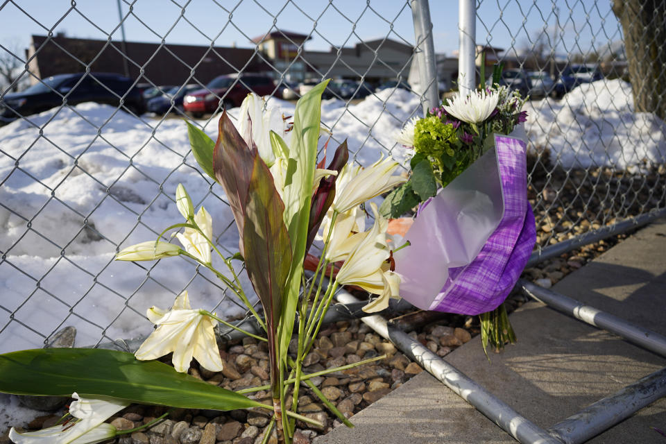 A small memorial stands along a makeshift fence put up around the parking lot outside a King Soopers grocery store where a mass shooting took place Tuesday, March 23, 2021, in Boulder, Colo. (AP Photo/David Zalubowski)