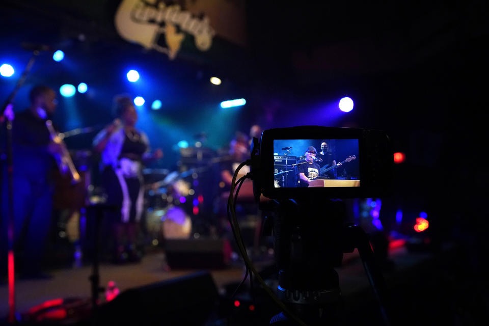 In this Oct. 26, 2020, photo, Ivan Neville is seen on a camera monitor sitting in with the band Galactic, as they record for a video stream concert, inside an empty Tipitina's music club, which the band owns, in New Orleans. Music clubs all over the nation — pop culture icons like the Troubadour in West Hollywood, the Bluebird Cafe in Nashville, The Bitter End in New York's Greenwich Village — are shuttered due to the coronavirus. And owners fear for the future of their businesses and of a musical way of life. (AP Photo/Gerald Herbert)