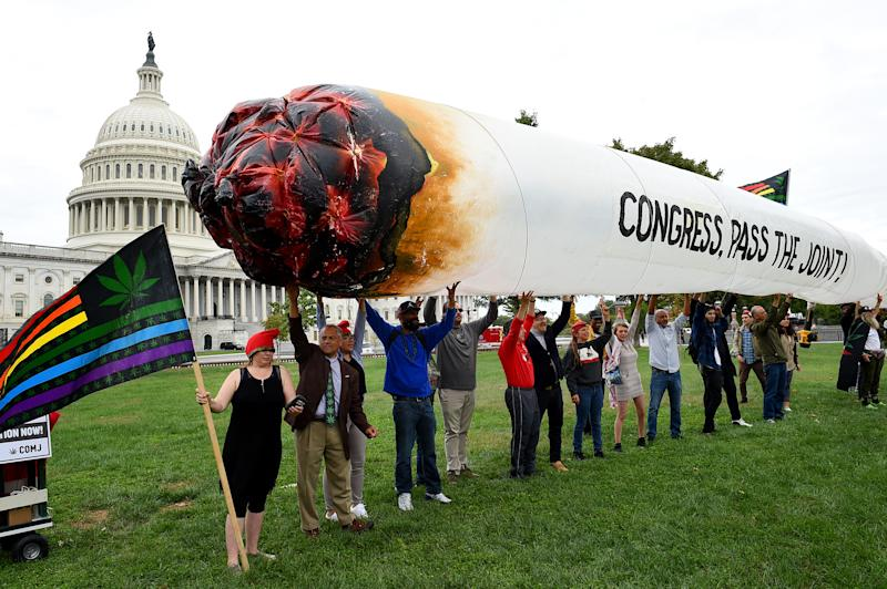 Activists from the DC Marijuana Justice (DCJM) hold a giant marijuana joint to demand Congress to pass cannabis reform legislation on the East Lawn of the US Capitol in Washington, DC on October 8, 2019. (Photo by Olivier Douliery / AFP) (Photo by OLIVIER DOULIERY/AFP via Getty Images)