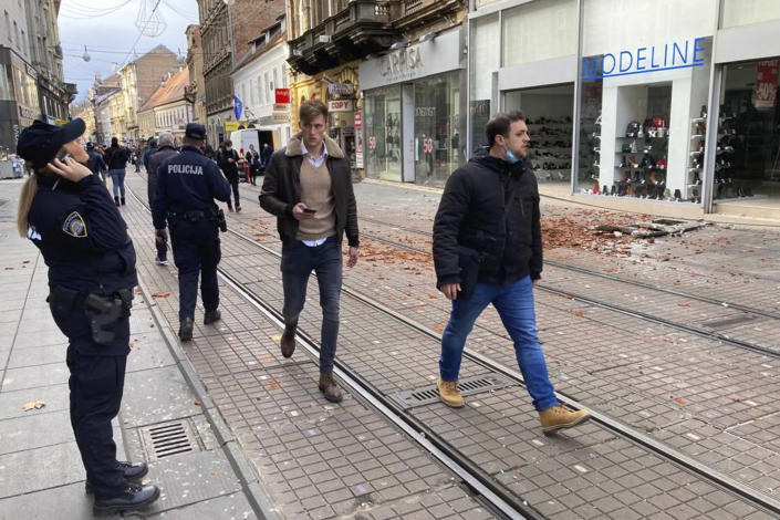 Residents walk past debris caused by an earthquake in downtown Zagreb, Croatia, Tuesday, Dec. 29, 2020. A strong earthquake hit Croatia on Tuesday, with some injuries reported as well as considerable damage to roofs and buildings southeast of the capital. (AP Photo/Filip Horvat)