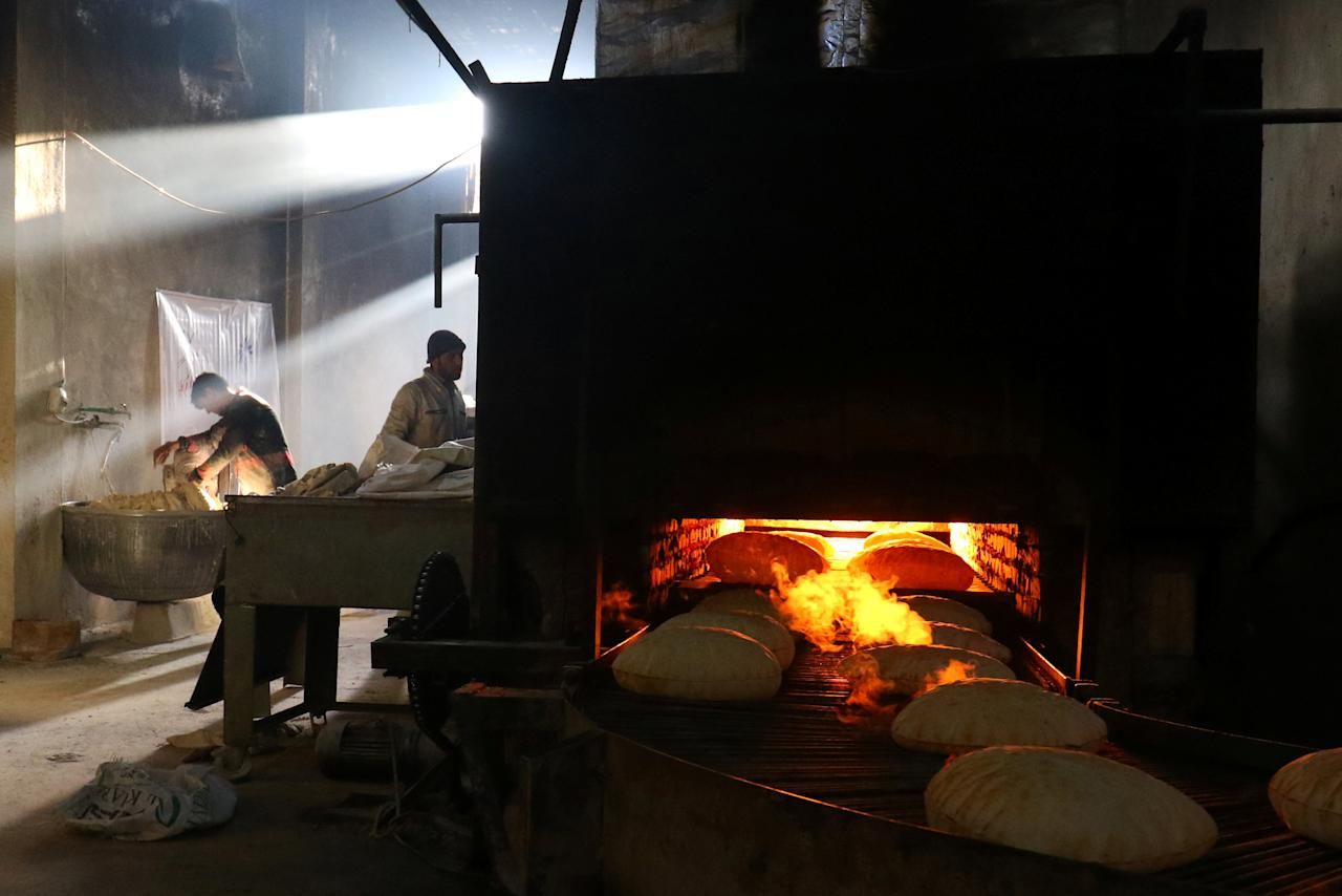 Men bake bread to be distributed free among internally displaced people in Salqin town, in Idlib province, Syria March 21, 2017. REUTERS/Ammar Abdullah
