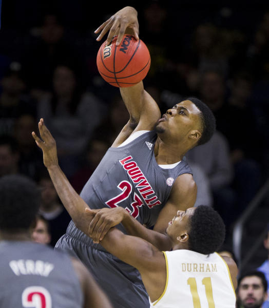 Louisville's Steven Enoch (23) grabs a rebound over Notre Dame's Juwan Durham (11) during the first half of an NCAA college basketball game Saturday, Jan. 11, 2020, in South Bend, Ind. (AP Photo/Robert Franklin)