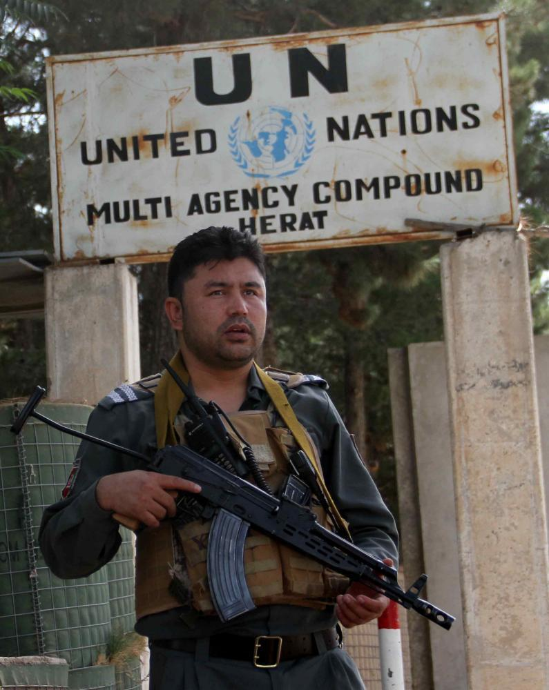 An Afghan security official standing guard outside the UN office in Herat