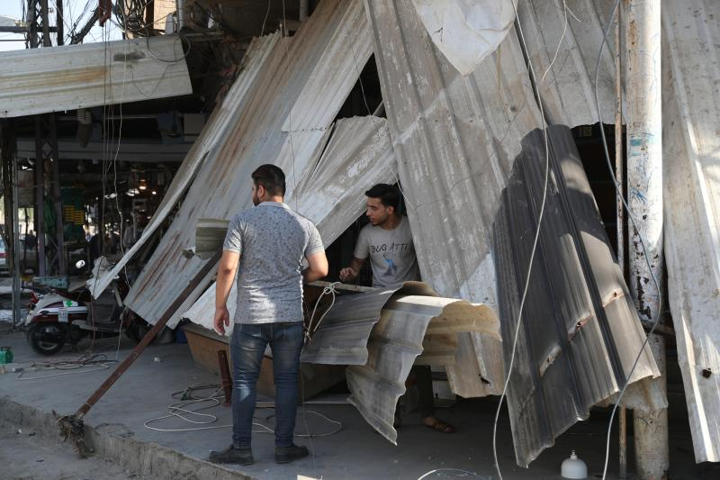 Shop owners survey the damage to their shops a day after a motorcycle rigged with explosives blew up in Mussayyib, south of Baghdad, Iraq, Saturday, Aug. 29, 2019. The officials said Saturday that the blast occurred the previous evening on a commercial street in the village of Mussayyib, killing and wounding civilians. (AP Photo/Khalid Mohammed)