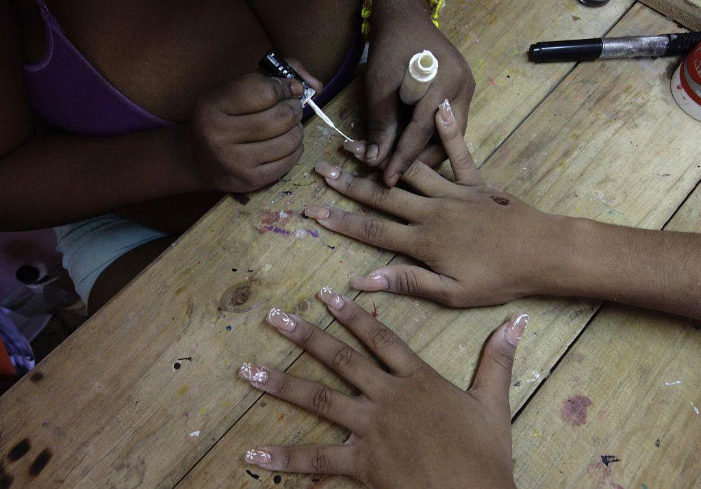 <p>Carmen Gonzalez has her nails manicured as she prepares for her quinceanera.</p>