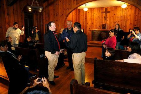 FILE PHOTO: Darren Black Bear (R) reads his vows from his cellphone to Jason Pickel (L) as they are married by Darren's father Rev. Floyd Black Bear (C) in El Reno, Oklahoma October 31, 2013. REUTERS/Rick Wilking/File Photo