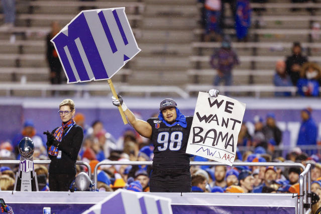 Boise State nose tackle Sonatane Lui (98) celebrates with a Mountain West and We Want Bama sign on the awards stand with Boise State President Marlene Tromp, left, after the Mountain West Championship game an NCAA college football game Saturday, Dec. 7, 2019, in Boise, Idaho. Boise State won 31-10. (AP Photo/Steve Conner)