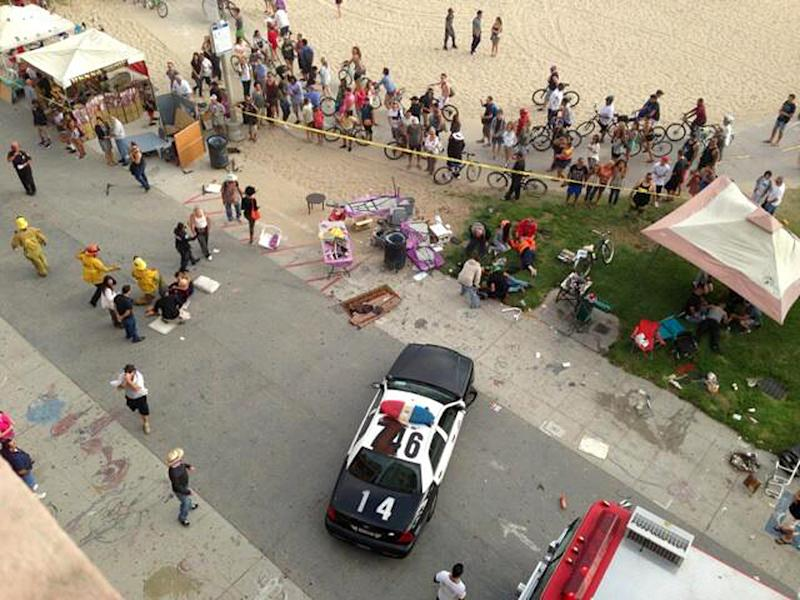 Pedestrians gather as police and fire officials respond after a car drove through a packed afternoon crowd along the Venice Beach boardwalk in Los Angeles, Saturday, Aug. 3, 2013. At least a dozen people were injured, two of them critically, according to police. (AP Photo/Maarten Smitskamp)