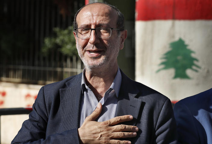 Hezbollah legal representative Ibrahim Mussawi gestures as he arrives to speak with journalists outside the Justice Palace in Beirut, Lebanon, Friday, Dec. 4, 2020. Lebanese Hezbollah said on Friday it is suing a former Christian lawmaker and a website affiliated with a Christian party for defamation after they accused the militant group of the massive explosion at the Beirut Port this summer. Hezbollah has denied any role in the Aug. 4 explosion that devastated Beirut and was caused by the detonation of nearly 3,000 of tons of explosive chemicals stored there for six years. (AP Photo/Hussein Malla)