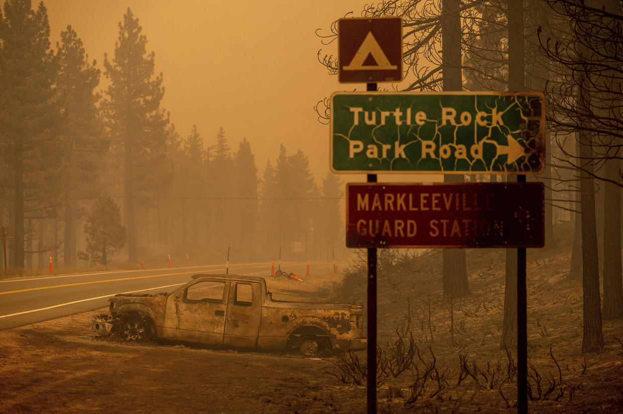 A scorched car rests on a roadside as the Tamarack Fire burns in Alpine County, Calif., on Saturday. (AP Photo/Noah Berger)