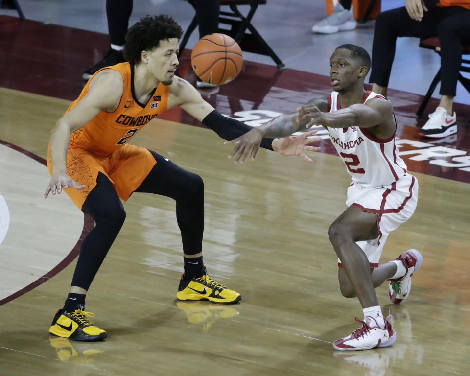 Oklahoma guard Umoja Gibson, right, passes the ball away from Oklahoma State guard Cade Cunningham, left, during the first half of an NCAA college basketball game, Saturday, Feb. 27, 2021, in Norman, Okla. (AP Photo/Garett Fisbeck)