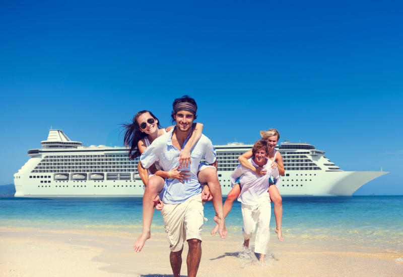 Two men carrying their girlfriends on their backs while frolicking in front of a anchored cruise ship