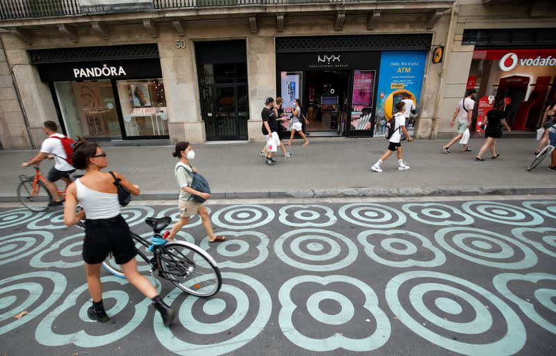 People walk by a pedestrian zone painted in blue at Pelai street in Barcelona