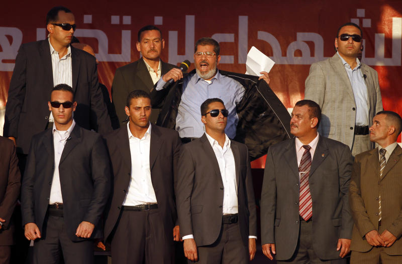"""FILE - In this Friday, June 29, 2012 file photo, Egypt's President-elect Mohammed Morsi, center, opens his jacket to show that he is not wearing a protective vest while he gives a speech at Tahrir Square in Cairo, Egypt. A statement on the Egyptian president's office's Twitter account has quoted Mohammed Morsi as calling military measures """"a full coup."""" The denouncement was posted shortly after the Egyptian military announced it was ousting Morsi, who was Egypt's first freely elected leader but drew ire with his Islamist leanings. The military says it has replaced him with the chief justice of the Supreme constitutional Court, called for early presidential election and suspended the Islamist-backed constitution.(AP Photo/Khalil Hamra, File)"""
