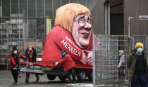 A political carnival float depicting German chancellor Angela Merkel and her possible successor Governor Armin Laschet is rolled out to be shown in the streets of Duesseldorf, Germany, Monday, Feb. 15, 2021. Because of the coronavirus pandemic the traditional; carnival parades are canceled but eight floats are pulled through the empty streets in Duesseldorf, where normally hundreds of thousands of people would celebrate the street carnival. (AP Photo/Martin Meissner)