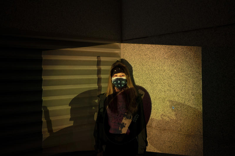 "A protester who identified herself as Cindy, poses for a portrait as a projector displays a photograph, previously taken during the unrest, over her at a protest in Hong Kong. An attempt last month to impose a city-wide mask ban only further inflamed the demonstrators, who now cover up in defiance. ""Wearing a mask right now is a statement against the Emergency Law,"" Cindy said. (Photo: Felipe Dana/AP)"