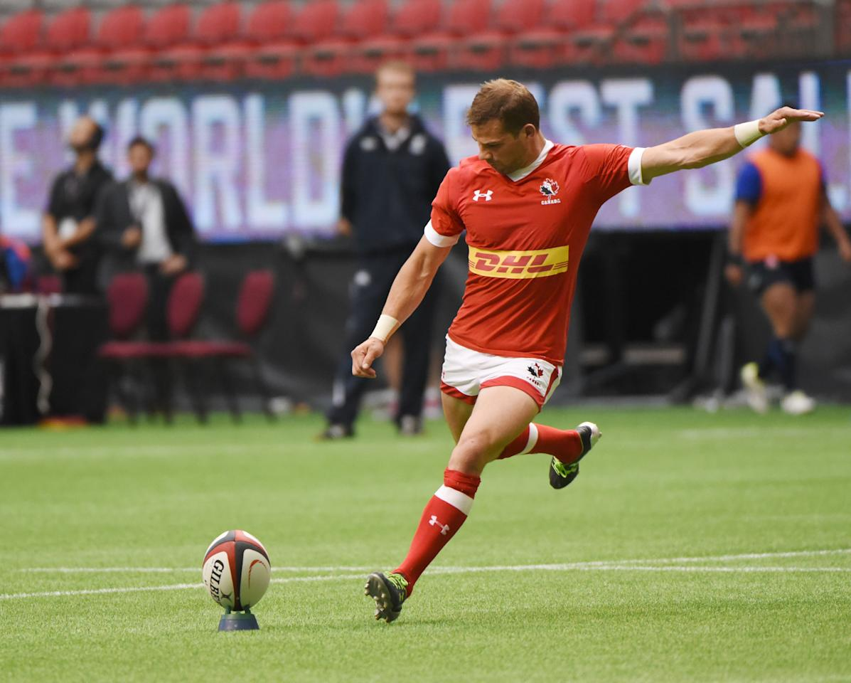 Canada's (red) #9 Gordon McRorie kicks a convertion vs Japan (blue) in a men's rugby action test match at BC Place, in Vancouver BC, on June 11, 2016.Japan won 26-22 over Canada in a hard fought game. (AFP Photo/Don MacKinnon)