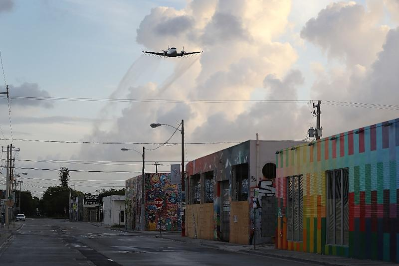 A plane sprays pesticide over the Wynwood neighborhood in the hope of controlling and reducing the number of mosquitos, some of which may be capable of spreading the Zika virus on August 6, 2016 in Miami, Florida (AFP Photo/Joe Raedle)