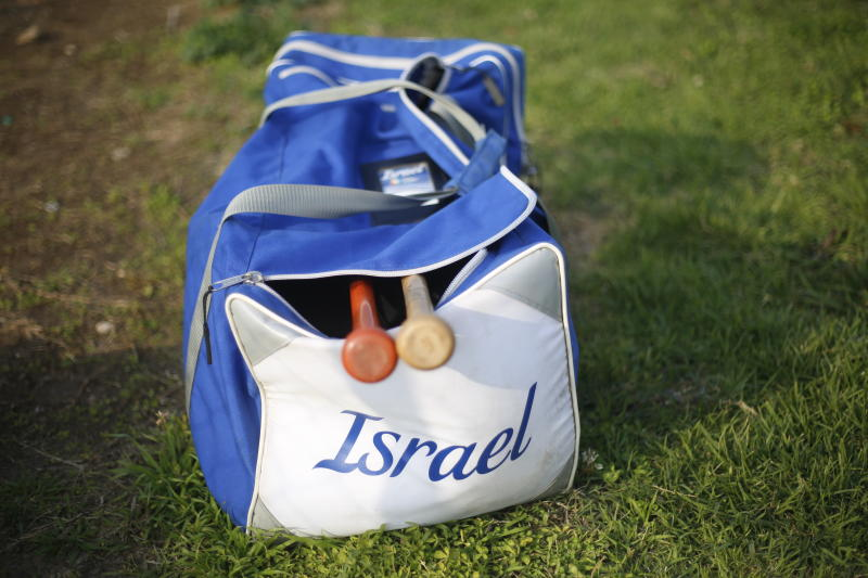 In this Tuesday, Jan. 14, 2020 photo, baseball equipment lies on the ground during an Israeli national baseball team practice, in Tel Aviv, Israel. Team Israel's improbable run to the Tokyo Olympic Games is spurring hope that it will provide the overlooked sport of baseball in Israel its long-awaited boost. Baseball is returning to the Olympics after being dropped for 2012 and 2016 and Israel is one of six teams vying for the three medals. (AP Photo/Ariel Schalit)
