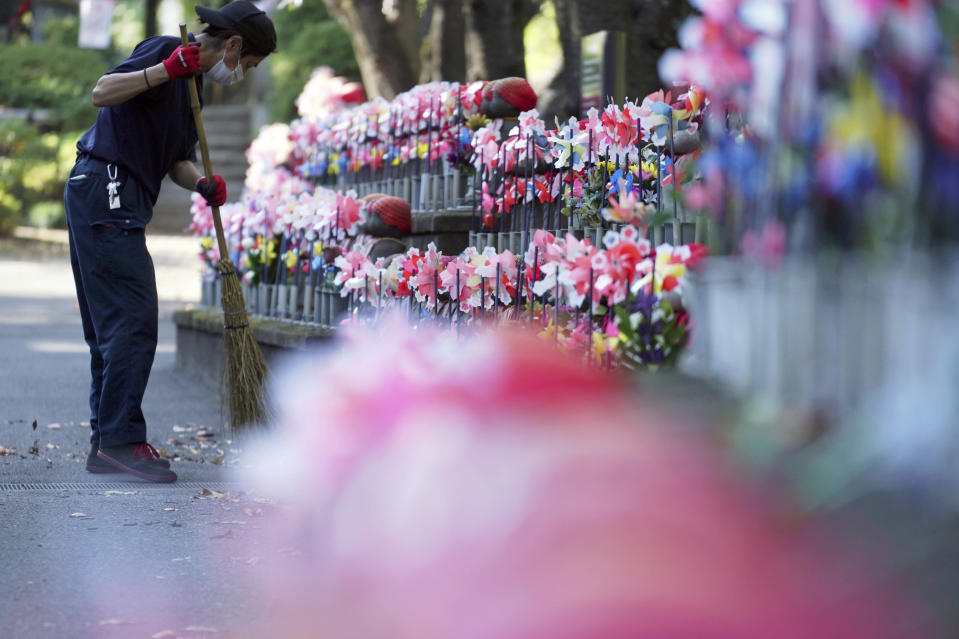 "An employee wearing a protective mask to help curb the spread of the coronavirus sweeps near pinwheels whirl in the breeze at rows of small stone statues of ""jizo"" representing the unborn children at a temple in Tokyo Thursday, Oct. 29, 2020. The Japanese capital confirmed more than 220 new coronavirus cases on Thursday. (AP Photo/Eugene Hoshiko)"