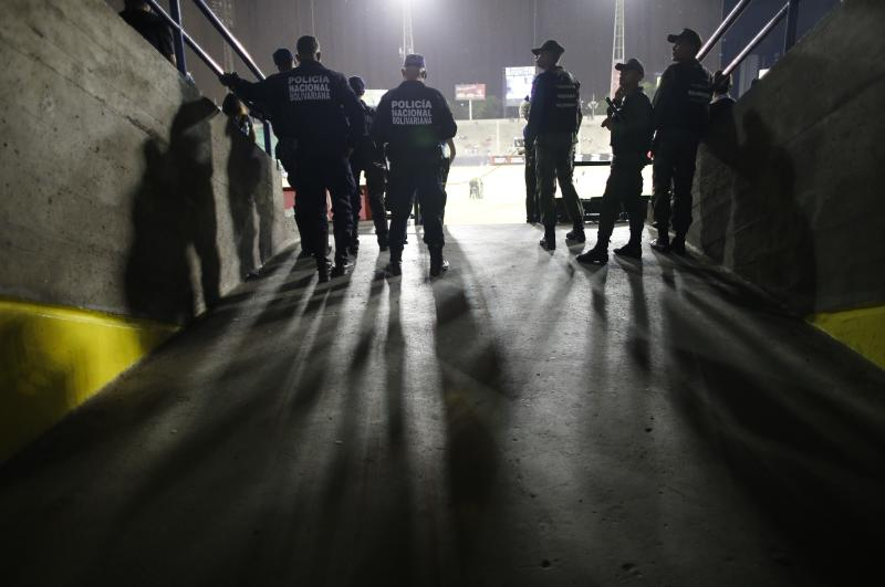 National Police and National Guards keep watch during the opening winter season game between Leones de Caracas and Tigres de Aragua in Caracas, Venezuela, Tuesday, Nov. 5, 2019. This season came at the end of a tumultuous year for Venezuelans and the nation's crisis has no end in sight. (AP Photo/Ariana Cubillos)