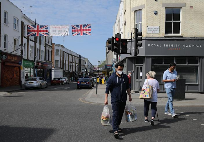 A man wearing personal protective equipment (PPE) shops in Portobello Road, west London, as the UK continues in lockdown to help curb the spread of the coronavirus. Picture date: Sunday April 26, 2020.