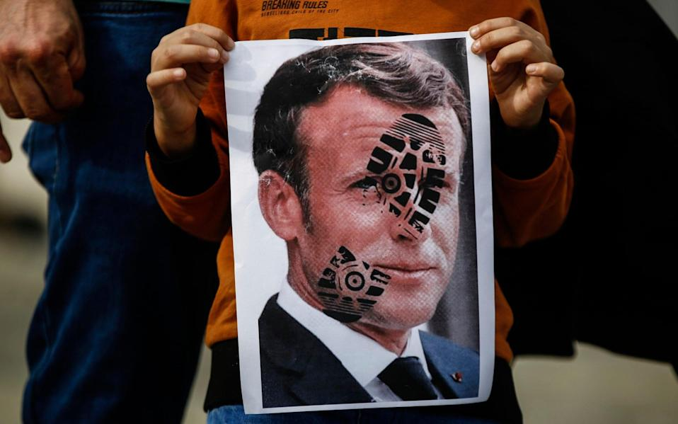 A child holds a photograph of Emmanuel Macron, stamped with a shoe mark, during a protest against France in Istanbul - AP Photo/Emrah Gurel
