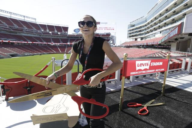Mahelly Ferreira unpacks a large pair of scissors to be used in a photo booth before the ribbon-cutting and opening of Levi's Stadium Thursday, July 17, 2014, in Santa Clara, Calif. The San Francisco 49ers held a ribbon-cutting ceremony to officially open their new home. The $1.2 billion Levi's Stadium, which took only about 27 months to build, also will host the NFL Super Bowl in 2016 and other major events. (AP Photo/Eric Risberg)