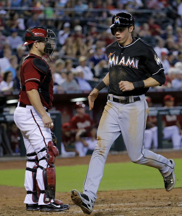 Miami Marlins' Christian Yelich, right, scores on a sacrifice by teammate Giancarlo Stanton as Arizona Diamondbacks catcher Miguel Montero looks away during the sixth inning of a baseball game, Wednesday, July 9, 2014, in Phoenix. (AP Photo/Matt York)