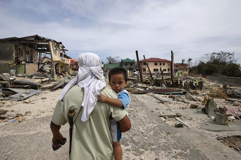 A man walks home with his son Monday Nov. 11, 2013 following Friday's devastating typhoon that lashed Hernani township, Eastern Samar province, central Philippines. Typhoon-ravaged Philippine islands faced an unimaginably huge recovery effort that had barely begun Monday, as bloated bodies lay uncollected and uncounted in the streets and survivors pleaded for food, water and medicine. (AP Photo/Bullit Marquez)