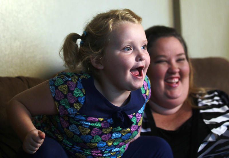 """In this photo taken Monday, Sept. 10, 2012, seven-year-old beauty pageant regular and reality show star Alana """"Honey Boo Boo"""" Thompson speaks during an interview as her mother June Shannon looks on in her home in McIntyre, Ga. The round-cheeked second-grader, who previously appeared on the TLC show """"Toddlers & Tiaras,"""" has a penchant for outrageous catchphrases as seen on her reality TV show, """"Here Comes Honey Boo Boo."""" (AP Photo/John Bazemore)"""