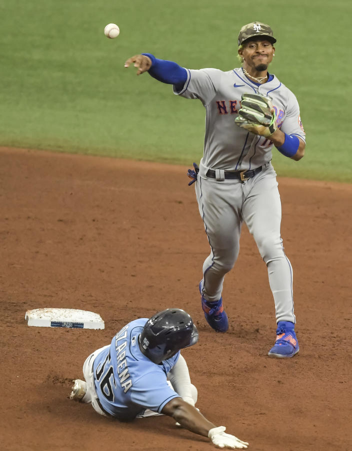 New York Mets shortstop Francisco Lindor, right, throws to first for a double play after forcing out Tampa Bay Rays' Randy Arozarena, left, at second base during the fifth inning of a baseball game Sunday, May 16, 2021, in St. Petersburg, Fla. (AP Photo/Steve Nesius)