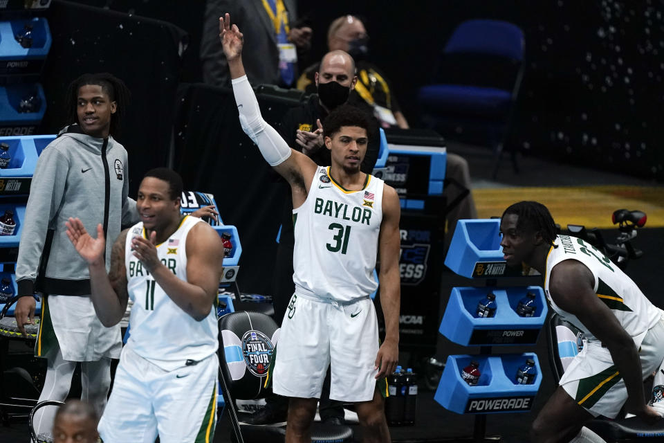 Baylor guard Mark Vital (11), MaCio Teague (31) and Jonathan Tchamwa Tchatchoua, right, celebrate on the bench during the first half of a men's Final Four NCAA college basketball tournament semifinal game against Houston, Saturday, April 3, 2021, at Lucas Oil Stadium in Indianapolis. (AP Photo/Michael Conroy)