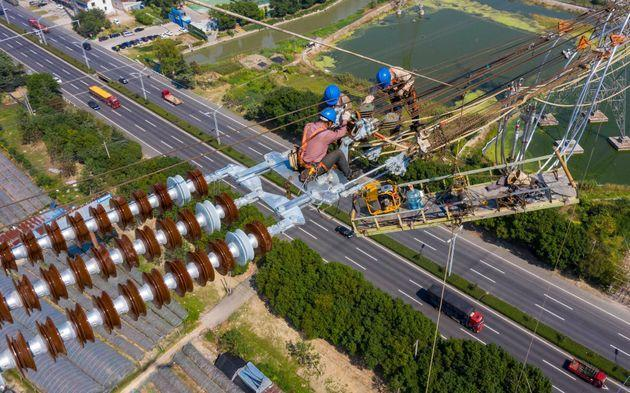 This photo taken on September 27, 2021 shows employees working on high-voltage direct current transmission line in Wuxi, in China's eastern Jiangsu province. - China OUT (Photo by STR / AFP) / China OUT (Photo by STR/AFP via Getty Images) (Photo: STR via Getty Images)