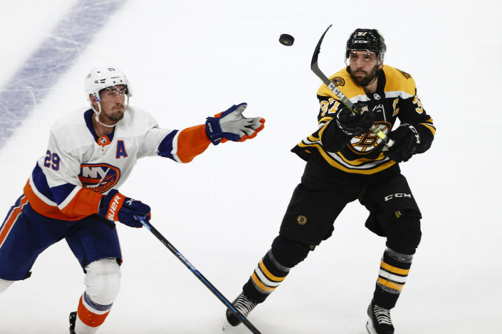 Boston Bruins' Patrice Bergeron and New York Islanders' Brock Nelson go for a loose puck in the second period of Game 2 during an NHL hockey second-round playoff series, Monday, May 31, 2021, in Boston. (AP Photo/Winslow Townson)