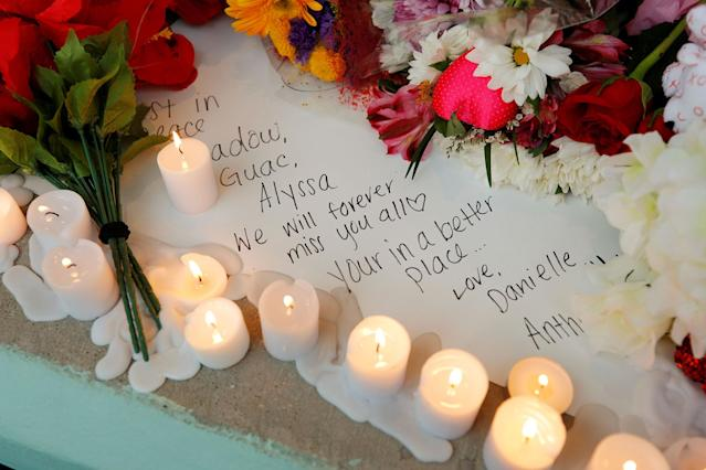 <p>A handwritten note to a lost friend is surrounded by candles and flowers at a candlelight vigil the day after a shooting at Marjory Stoneman Douglas High School in Parkland, Fla., Feb. 15, 2018. (Photo: Jonathan Drake/Reuters) </p>