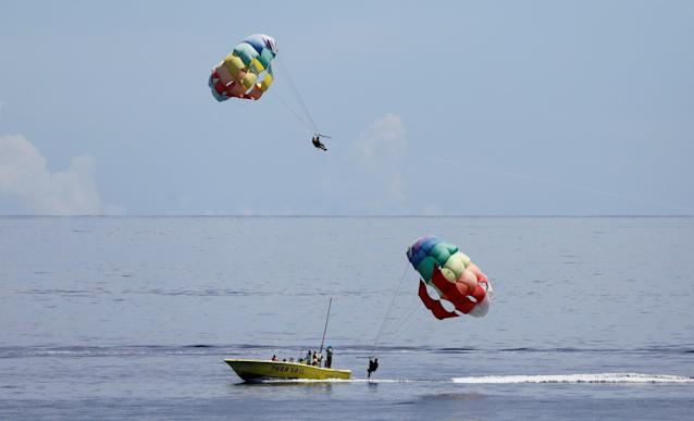 <p>Tourists take part in parasail off the waters of Tumon beach on the island of Guam, a U.S. Pacific Territory, August 10, 2017. (Erik De Castro/Reuters) </p>